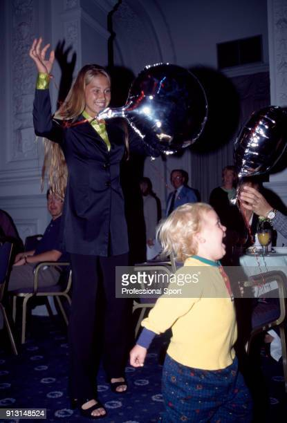 Anna Kournikova of Russia entertaining a toddler with balloons at an event during the Wimbledon Lawn Tennis Championships at the All England Lawn...