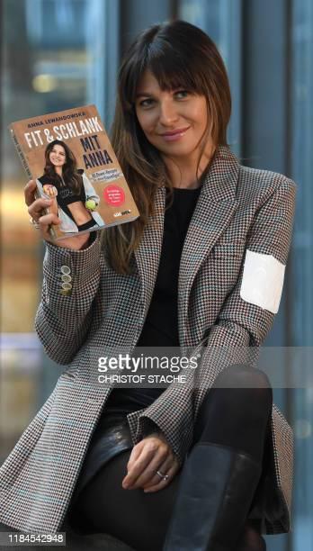 Anna Lewandowska wife of Bayern Munich's Polish striker Robert Lewandowski poses with her new sport and fitness book Fit und Schlank mit Anna in...