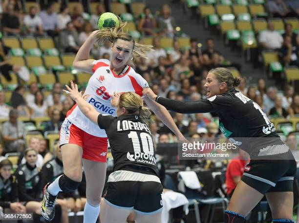 Anna Loerper and Julia Behnke of Germany challenge Kinga Achruk of Poland for the ball during the Women's handball International friendly match...