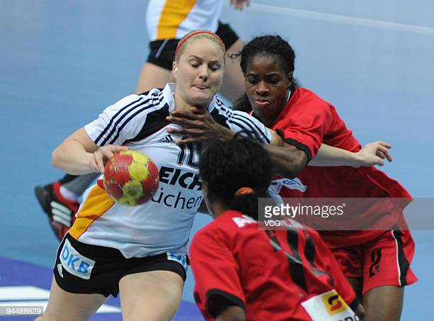 Anna Loerper of Germany is blocked by Angola players during the main round match between Angola and Germany at Yangzhou Stadium on day eleven of the...