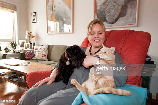 Anna Margret Bjarnadottir holds her pet dog and cat in her house on March 2 2010 in Mosfellsbaer on the outskirts of Reykjavik Unemployed and...