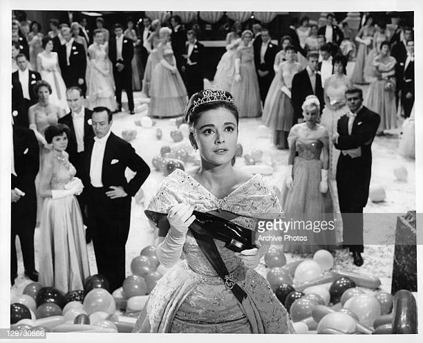 Anna Maria Alberghetti holding man's shoe and looking up in a scene from the film 'Cinderfella' 1960