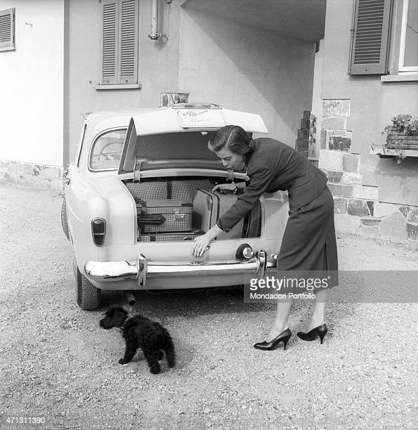 Anna Maria Ferrero the artistic name of Anna Maria Guerra bends over to put a suitcase in the boot of her Alfa Romeo Giulietta She waves at a small...