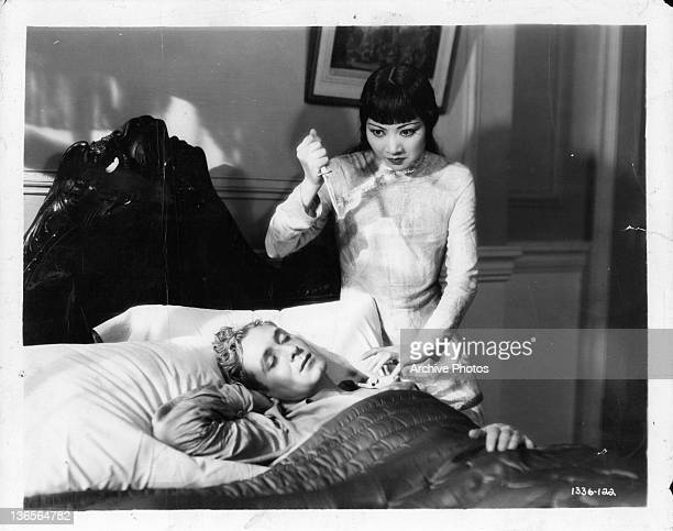 Anna May Wong about to stab a sleeping man in a scene from the film 'Daughter Of The Dragon' 1931
