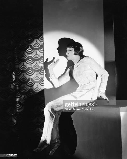 Anna May Wong US actress wearing a longsleeve long white dress gesticulating with right arm with her shadow cast against the wall behind her in a...