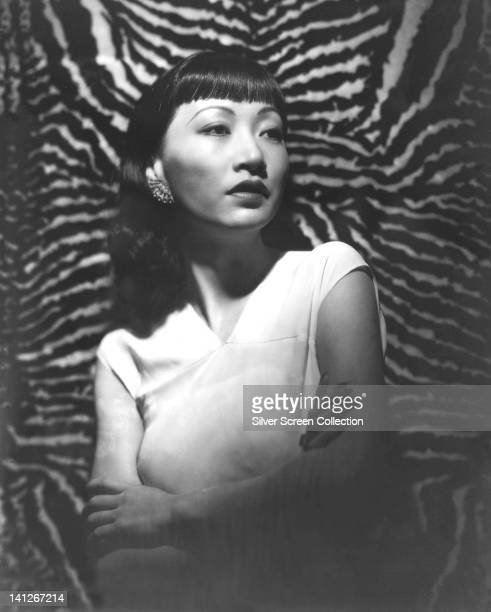 Anna May Wong US actress wearing a sleeveless white top posing with her arms folded in a dramaticallylit studio portrait against a tiger skin...
