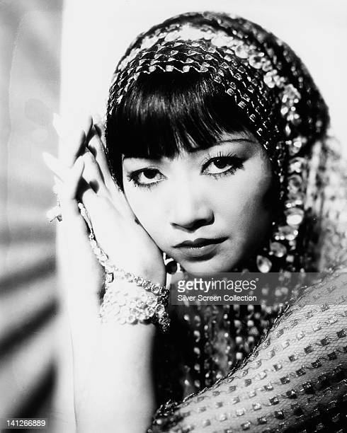Anna May Wong US actress with her hands held to the side of her head wearing a jewelled shawl in a studio portrait circa 1930