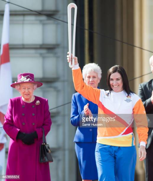 Anna Meares carries the Commonwealth baton as Queen Elizabeth II looks on during the launch of The Queen's Baton Relay for the XXI Commonwealth Games...