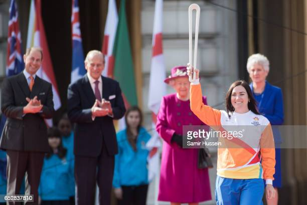Anna Meares carries the Commonwealth baton as Queen Elizabeth II Prince Philip Duke of Edinburgh and Prince Edward Earl of Wessex look on during the...