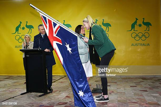 Anna Meares is presented with the Australian flag by Lauren Jackson flagbearer for the 2012 London Olympic Games during the Australian Olympic Games...