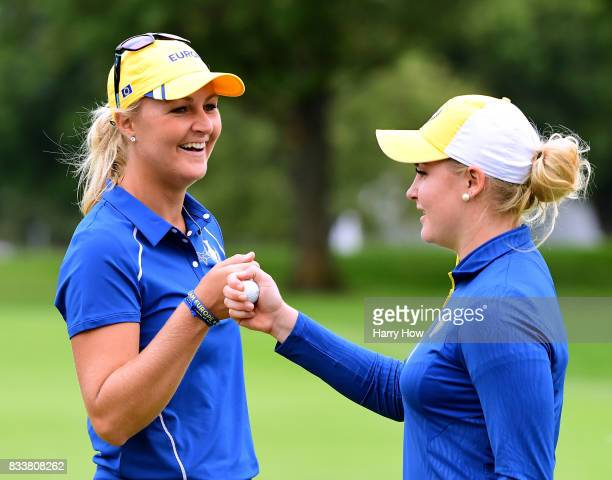 Anna Nordqvist of Team Europe and Charley Hull celebrate a putt on the 18th green during practice for the Solheim Cup at the Des Moines Golf and...