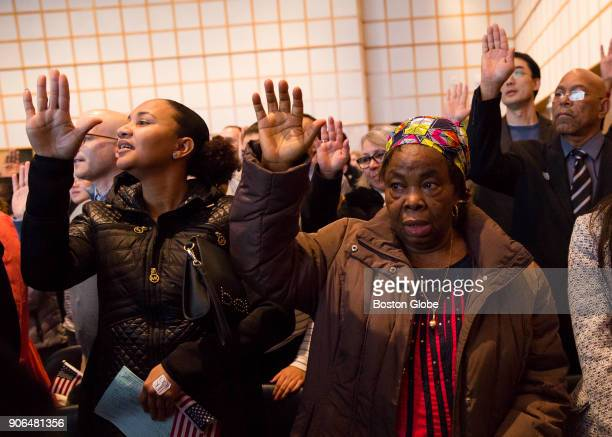 Anna Nwaibari Okoro right originally from Nigeria raises her hand as she takes the oath of citizenship during a naturalization ceremony at the John F...