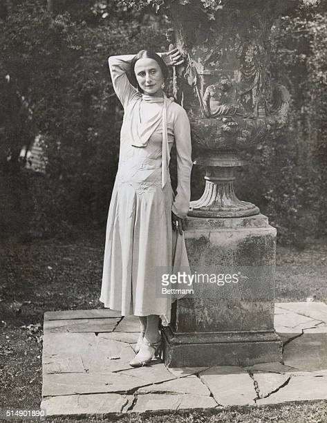 Anna Pavlova Russian ballerina in street clothes strikes a dramatic pose with a garden urn