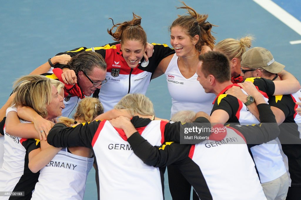 Anna Petkovic and Julia Goerges of Germany celebrate victory with team-mates during the Fed Cup Semi Final tie between Australia and Germany at Pat Rafter Arena on April 20, 2014 in Brisbane, Australia.