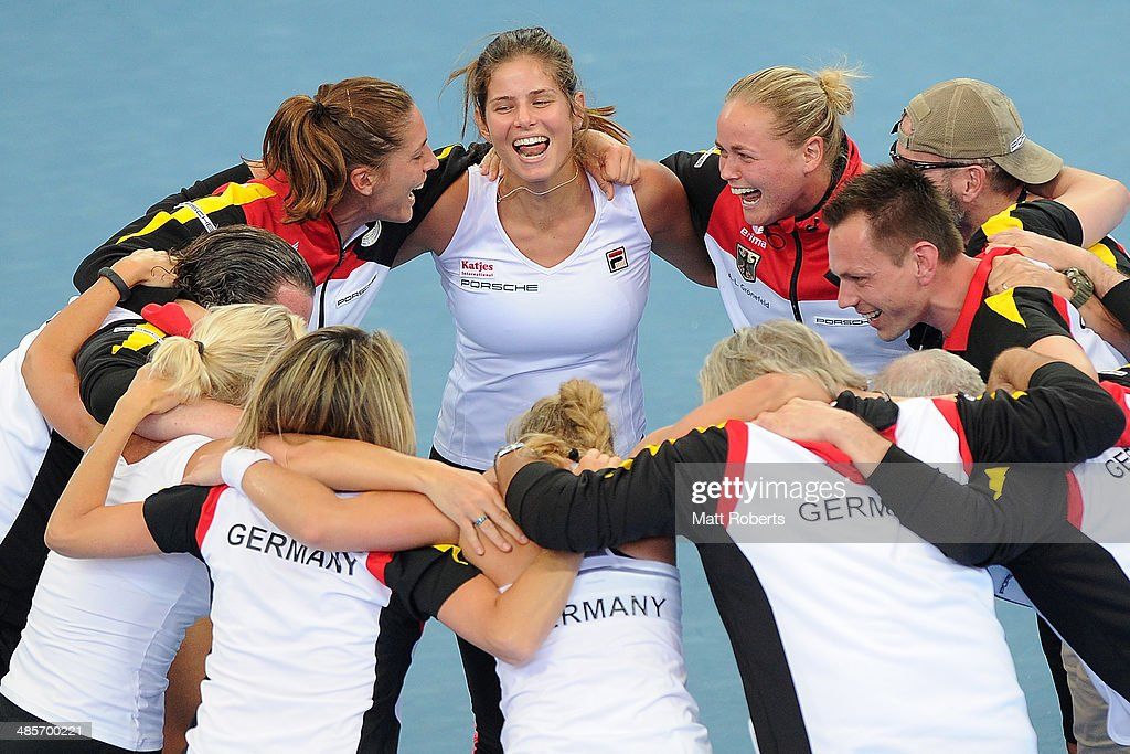 Anna Petkovic, Julia Goerges and Anna-Lena Groenefeld of Germany celebrate victory with team-mates during the Fed Cup Semi Final tie between Australia and Germany at Pat Rafter Arena on April 20, 2014 in Brisbane, Australia.