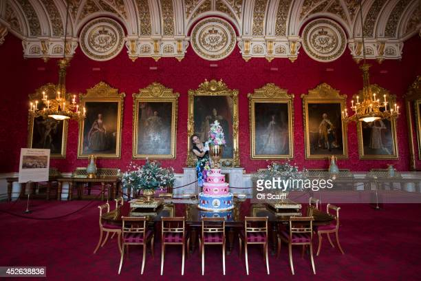 Anna Reynolds curator of Royal Collection Trust puts the finishing touches to a display of the 1853 christening cake of Prince Leopold in the State...