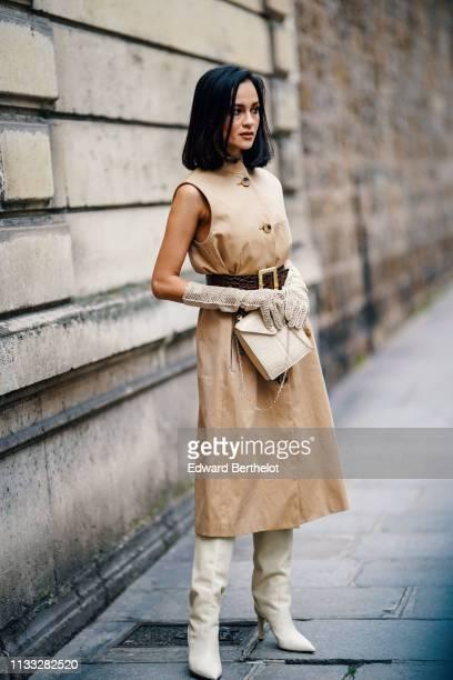 Anna Rosa Vitiello wears a beige dress a belt gloves white boots a bag outside Elie Saab during Paris Fashion Week Womenswear Fall/Winter 2019/2020...