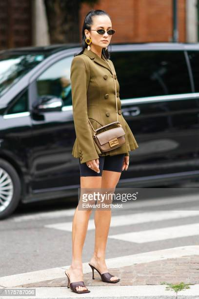 Anna Rosa Vitiello wears a green khaki jacket pleated dress, black shorts, a Fendi bag, brown leather shoes, outside the Fendi show during Milan...