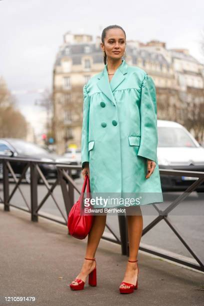 Anna Rosa Vitiello wears a green long double breasted coat/dress with buttons, a red leather bag, red shoes, outside Miu Miu, during Paris Fashion...