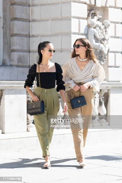 Anna Rosa Vitiello wears a Kurt Geiger bag, Reformation top, Maxine shoes, Topshop trousers and Linda Farrow sunglasses with Florrie Thomas wearing...