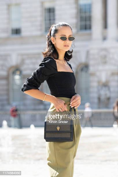 Anna Rosa Vitiello wears a Kurt Geiger bag, Reformation top, Topshop trousers and Linda Farrow sunglasses on September 13, 2019 in London, England.