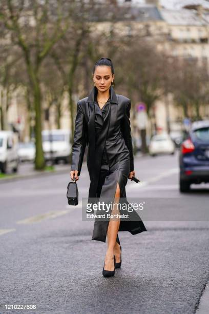 Anna Rosa Vitiello wears earrings, a necklace, a black leather side-split shirt dress with a lavaliere, a black handbag, black pointy heeled pumps ,...