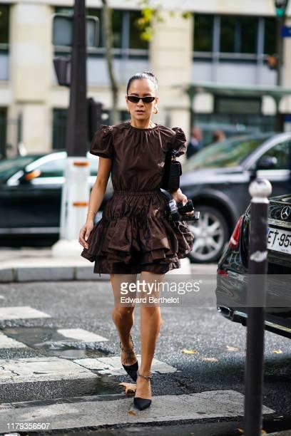 Anna Rosa Vitiello wears sunglasses, a brown ruffled dress, earrings, a bag, pointy shoes, outside Miu Miu, during Paris Fashion Week - Womenswear...