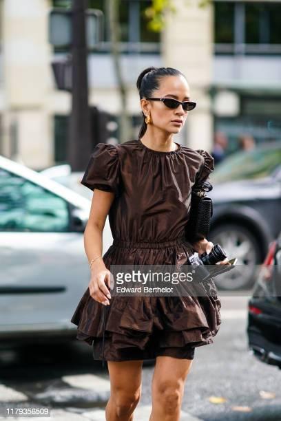Anna Rosa Vitiello wears sunglasses a brown ruffled dress earrings a bag outside Miu Miu during Paris Fashion Week Womenswear Spring Summer 2020 on...