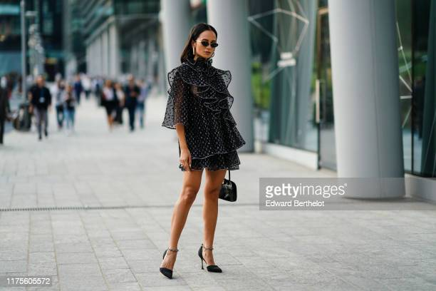 Anna Rosa Vitiello wears sunglasses a earrings a ruffled mesh lace dress with printed circles high heeled shoes outside the Alberta Ferretti show...