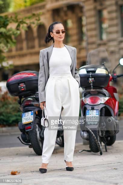 Anna Rosa Vitiello wears sunglasses, a light grey Prince of Wales check jacket, a white top, white pants, a white handbag, black pointy heeled pumps,...
