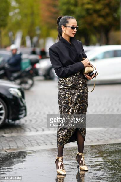 Anna Rosa Vitiello wears sunglasses, earrings, a lustrous black jacket, a Chanel black lamed long wrap skirt with gold-tone prints, a shiny gold tone...