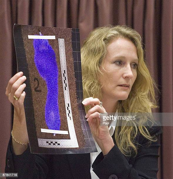 Anna Sandiford holds a picture of David Bain's bloodied foot treated with Luminol used during the tests during the continuation of David Bain's...