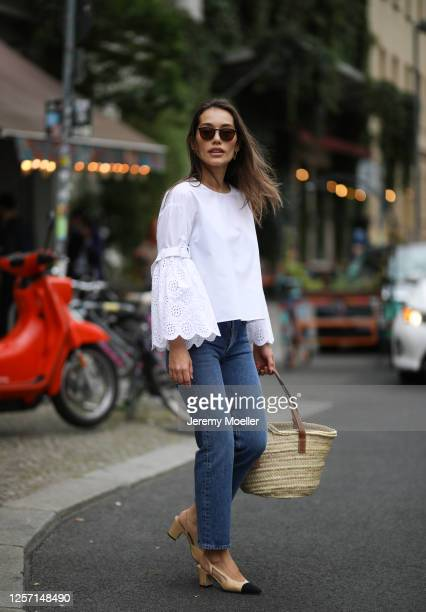 Anna Schürrle wearing Agolde jeans, Chanel heels, Loewe bag, Oliver People's shades and white blouse on July 17, 2020 in Berlin, Germany.