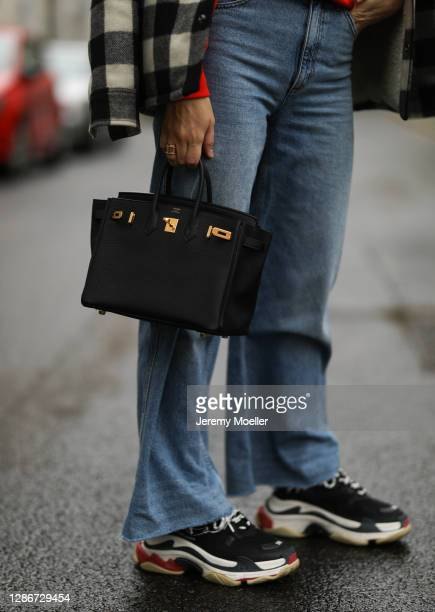 Anna Schürrle wearing black leather Hermès bag, red Vogue Sweater, Sandro pants and jacket and Balenciaga triple s on November 19, 2020 in Berlin,...