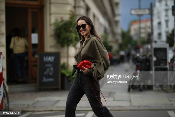 Anna Schürrle wearing Bottega Veneta shades and bag, Agolde jeans and Sosue blouse on July 17, 2020 in Berlin, Germany.