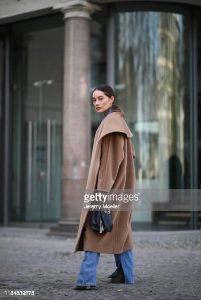 Anna Schürrle wearing Denim overall Ganni Max Mara coat Bvlgari bag Aeyde earrings Gianvito Rossi heels on October 31 2019 in Berlin Germany