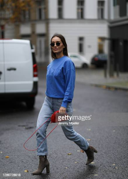 Anna Schürrle wearing Gianvito Rossi boots, Thome Browne shades and Citizens of Humanity jeans, blue Vogue sweater and red leather mini Bottega...
