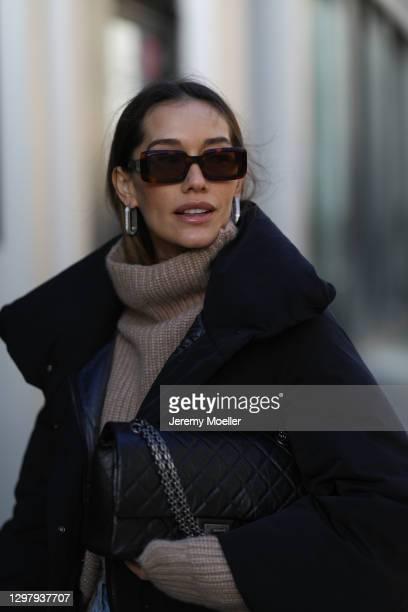 Anna Schürrle wearing Loewe shades, Chanel black leather bag, Anine Bing knit sweater and Uniqlo x Jil Sander black Puffer jacket on January 21, 2021...