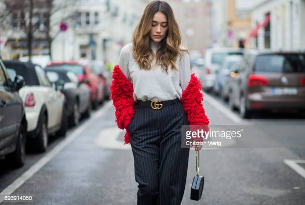 Anna Sharypova wearing Gucci belt grey HM turtleneck red jacket other stories navy striped HM pants Zara bag Buffalo heels on December 16 2017 in...