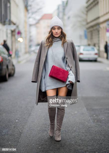 Anna Sharypova wearing Stuart Weitzman overknee boots a grey COS coat red Agneel bag grey COS turtleneck Acne wool beanie on December 16 2017 in...