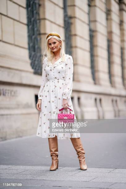 Anna Syren wears a tannish yellow headband earrings necklaces a pink studded handbag a black floral print flowing ruffled and gathered dress camel...