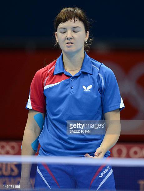 Anna Tikhomirova of Russia reacts after lsoing a point to Tan Wenling of Italy during their table tennis women's singles preliminary round match of...