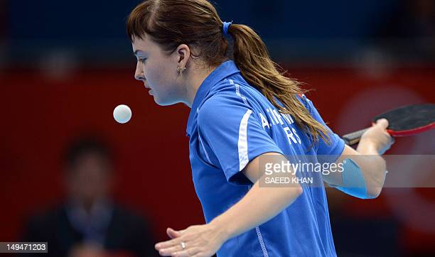 Anna Tikhomirova of Russia returns a shot to Tan Wenling of Italy during their table tennis women's singles preliminary round match of the London...