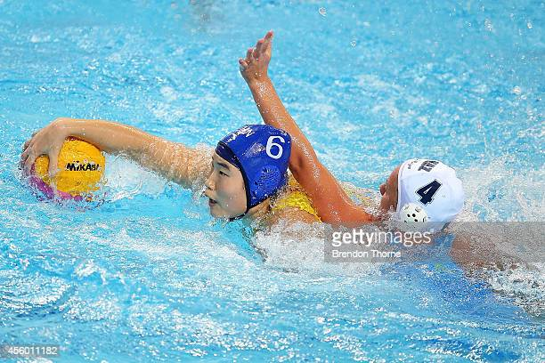 Anna Turova of Kazakhstan competes with Yating Sun of China in the Women's Single Round Robin Waterpolo during day five of the 2014 Asian Games at...