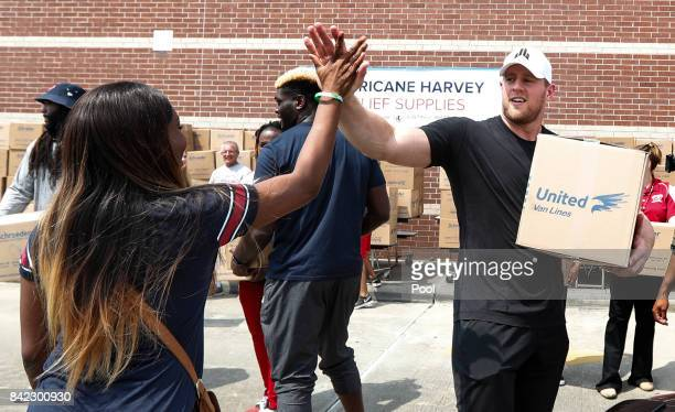 Anna Ucheomumu high fives Houston Texans defensive end JJ Watt after loading a car with relief supplies for people impacted by Hurricane Harvey on...