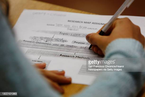 Anna Volshka fills in a research map assignment worksheet as she and her group work on a classroom exercise brainstorming a topic and research...