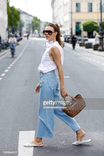 Anna von Schilcher, wearing a blouse without sleeves by Miu Miu, denim jeans by Iris & Ink and white slippers by Kennel & Schmenger during a street...