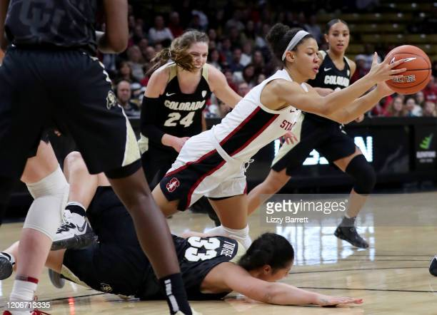 Anna Wilson of the Stanford Cardinal makes a rebound as she falls on top of Peanut Tuitele of the Colorado Buffaloes during the fourth quarter of a...