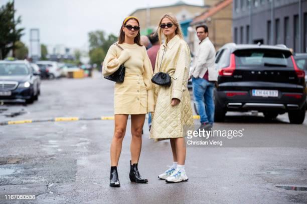 Anna Winter and Alyssa Winter wearing yellow coat, mini skirt, knit seen outside Baum und Pferdgarten during Copenhagen Fashion Week Spring/Summer...