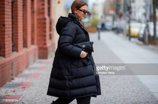 Anna Winter is seen wearing Valentino sunglasses, black puffer jacket &Other Stories, creme white knit Pepe Jeans, black Weekday pants, Prada bag on...
